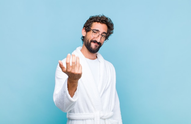 Young bearded man wearing a bath robe feeling happy, successful and confident, facing a challenge and saying bring it on! or welcoming you