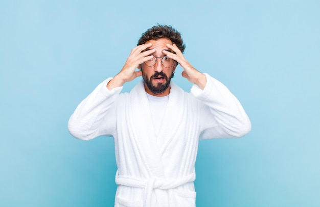 Young bearded man wearing a bath robe feeling horrified and shocked, raising hands to head and panicking at a mistake