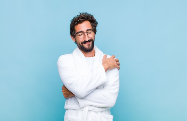 Young bearded man wearing a bath robe feeling in love, smiling, cuddling and hugging self, staying single, being selfish and egocentric