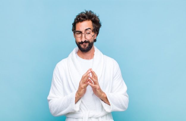 Young bearded man wearing a bath robe feeling proud, mischievous and arrogant while scheming an evil plan or thinking of a trick