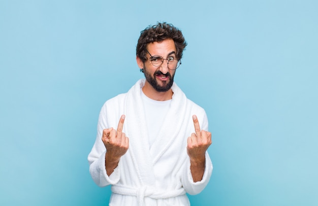 Young bearded man wearing a bath robe feeling provocative, aggressive and obscene, flipping the middle finger, with a rebellious attitude
