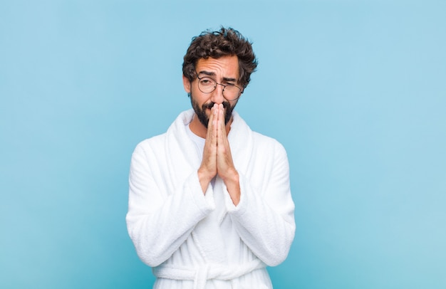 Young bearded man wearing a bath robe feeling worried, hopeful and religious, praying faithfully with palms pressed, begging forgiveness