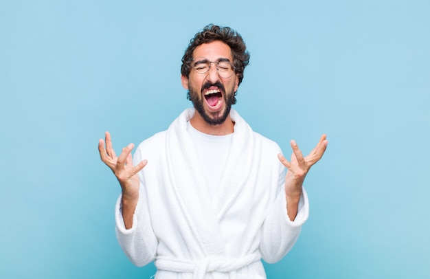 Young bearded man wearing a bath robe furiously screaming, feeling stressed and annoyed with hands up in the air saying why me