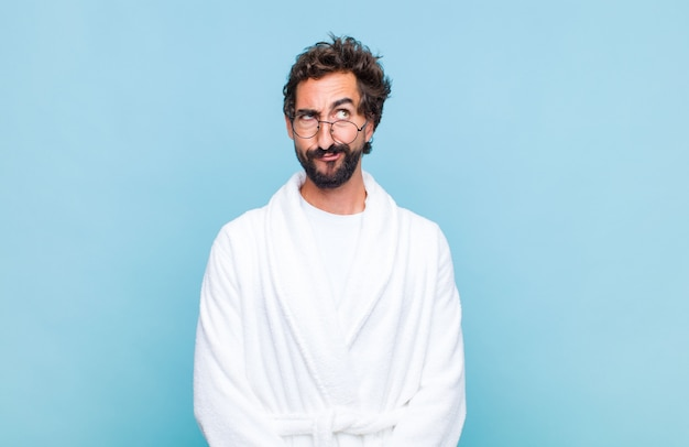 Young bearded man wearing a bath robe looking puzzled and confused, wondering or trying to solve a problem or thinking
