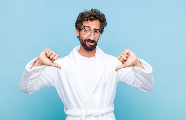 Young bearded man wearing a bath robe looking sad, disappointed or angry, showing thumbs down in disagreement, feeling frustrated