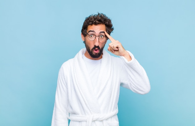 Young bearded man wearing a bath robe looking surprised, open-mouthed, shocked, realizing a new thought