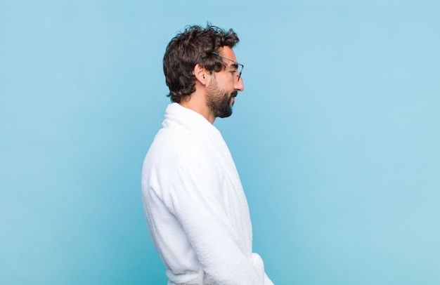 Young bearded man wearing a bath robe on profile view looking to copy space ahead, thinking, imagining or daydreaming