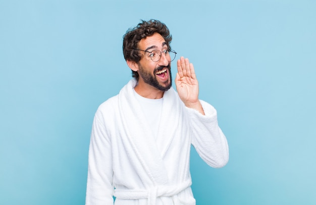 Young bearded man wearing a bath robe profile view, looking happy and excited