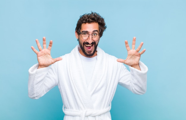 Young bearded man wearing a bath robe screaming in panic or anger, shocked, terrified or furious, with hands next to head