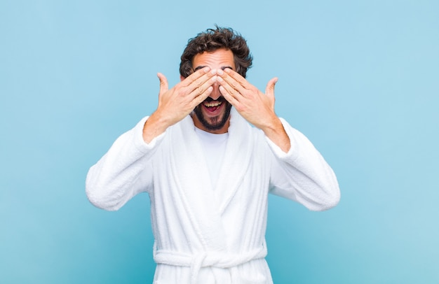 Young bearded man wearing a bath robe smiling and feeling happy, covering eyes with both hands and waiting for unbelievable surprise