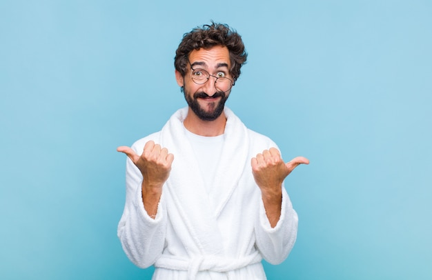 Young bearded man wearing a bath robe smiling joyfully and looking happy, feeling carefree and positive with both thumbs up