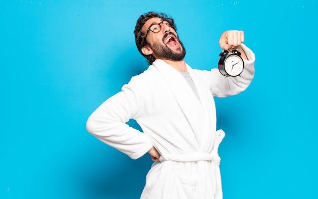 Young bearded man wearing bathrobe and an alarm clock