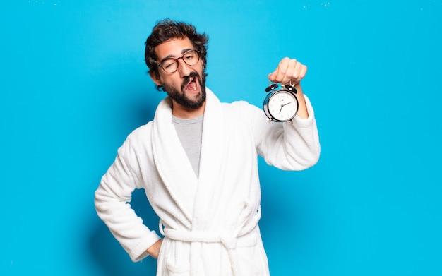バスローブと目覚まし時計を身に着けている若いひげを生やした男