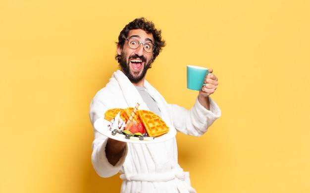 バスローブを着て朝食をとっている若いひげを生やした男