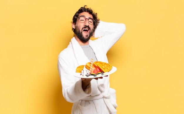 バスローブを着て朝食を食べている若いひげを生やした男