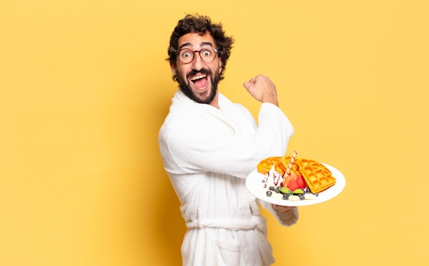 Молодой бородатый мужчина в халате и завтракает
