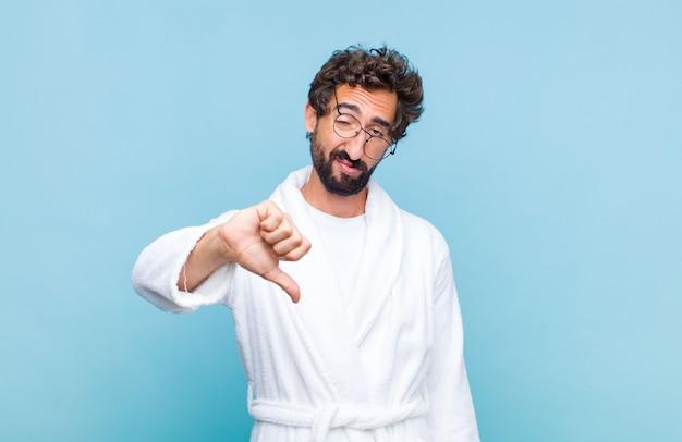 Young bearded man wearing a bathrobe feeling angry