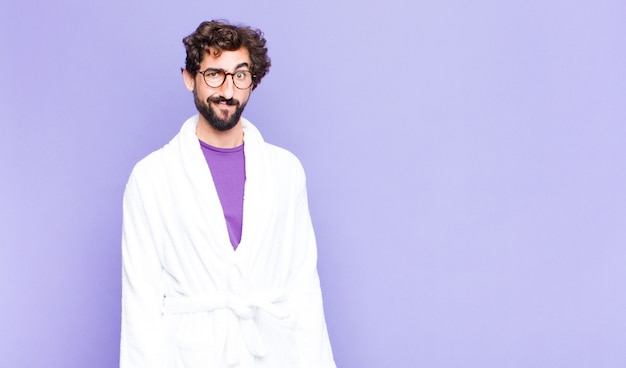 Young bearded man wearing bathrobe feeling confused and doubtful, wondering or trying to choose