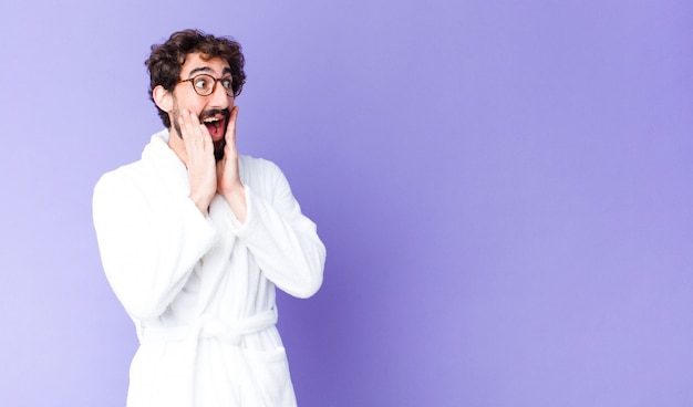 Young bearded man wearing bathrobe feeling happy, excited and surprised, looking to the side with both hands on face