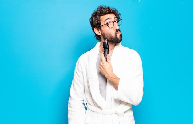 Young bearded man wearing bathrobe. hair or beard care concept