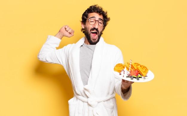 Young bearded man wearing bathrobe and having breakfast
