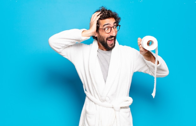 Young bearded man wearing bathrobe and role of toilet