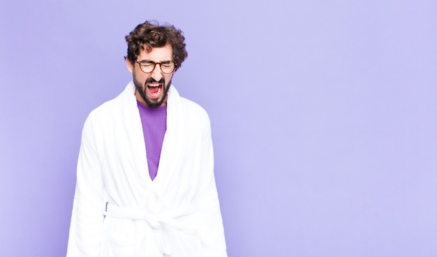 Young bearded man wearing bathrobe shouting aggressively, looking very angry, frustrated, outraged or annoyed, screaming no
