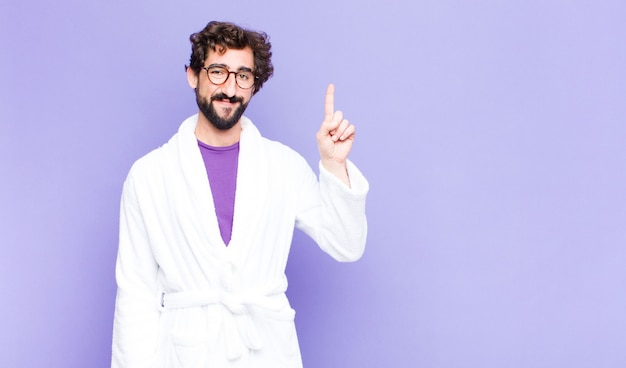 Young bearded man wearing bathrobe smiling cheerfully and happily, pointing upwards with one hand to copy space