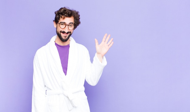 Young bearded man wearing bathrobe smiling happily and cheerfully, waving hand, welcoming and greeting you, or saying goodbye