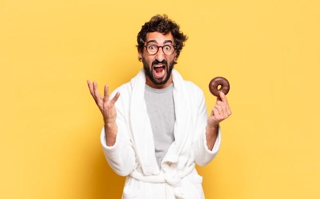 チョコレートドーナツとバスローブを着て若いひげを生やした男
