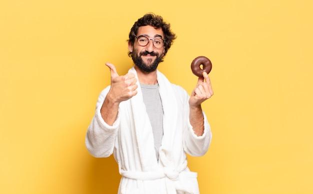 チョコレートドーナツとバスローブを着ている若いひげを生やした男