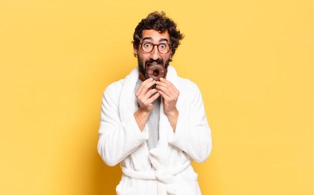 チョコレート ドーナツとバスローブを着た若いひげを生やした男