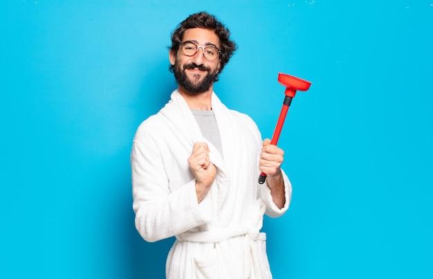 Молодой бородатый мужчина в халате с поршнем