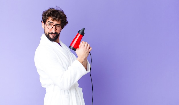 Young bearded man  wearing bathrobe with a hairdresser