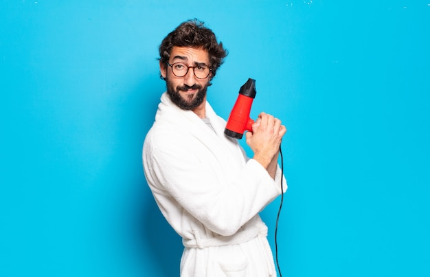 Young bearded man wearing bathrobe with a hairdryer