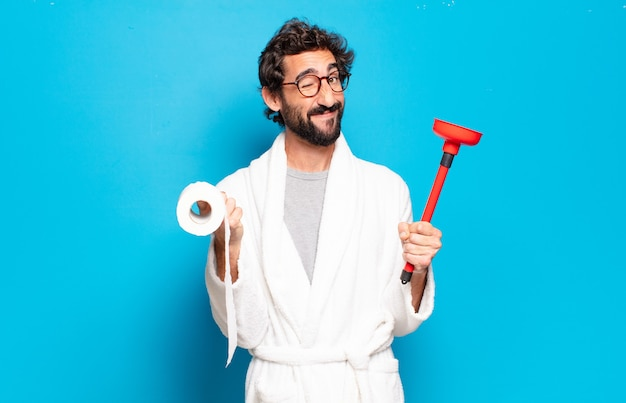 Young bearded man wearing bathrobe with a plunger