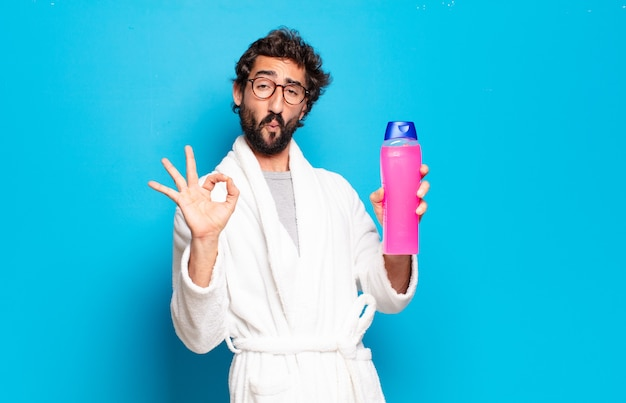 Young bearded man wearing bathrobe with shampoo and beauty products