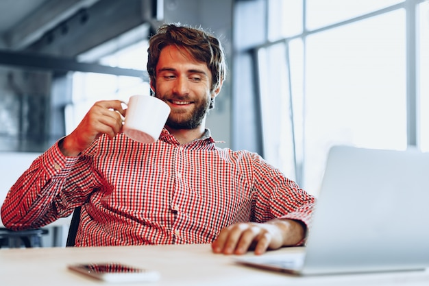 Young bearded man wearing casual shirt using his laptop computer. businessman portrait