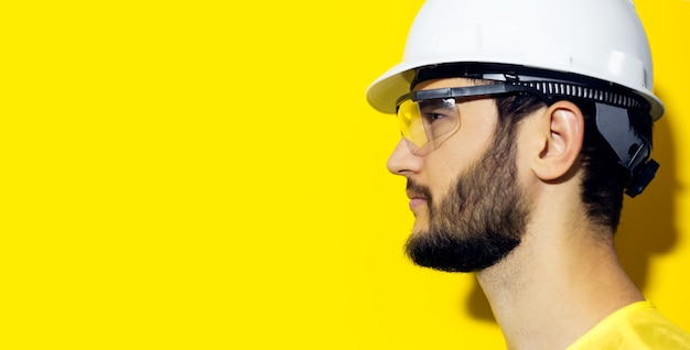 Young bearded man wearing construction safety helmet and glasses on yellow wall.