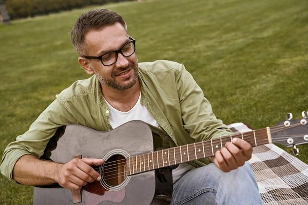 Молодой бородатый мужчина в очках играет на акустической гитаре, сидя на зеленой траве в парке