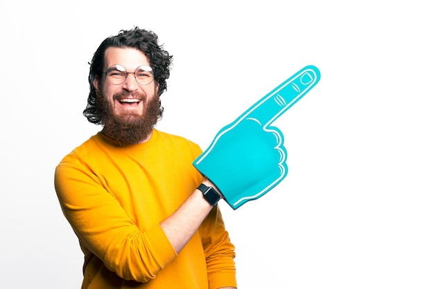 Young bearded man wearing round glasses is pointing with his fan foam glove.