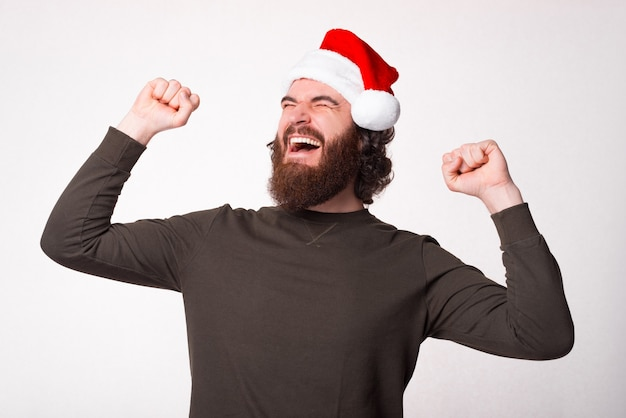 산타 클로스 모자를 쓰고 주먹으로 축하하는 수염 난 젊은이