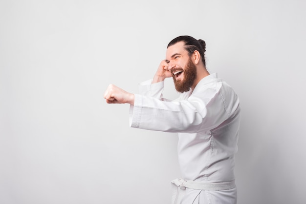 Young bearded man wearing taekwondo uniform punching over white wall