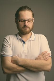 Молодой бородатый мужчина в белой рубашке поло