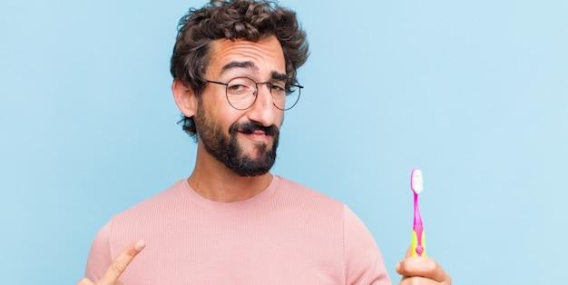 Молодой бородатый мужчина с плохим отношением выглядит гордым и агрессивным, указывая вверх или весело жест рукой