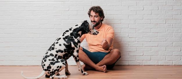 흰색 벽돌 벽에 달마 시안 강아지와 수염 된 젊은이