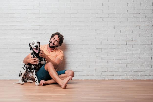 Молодой бородатый человек с собакой далматин против белой кирпичной стены