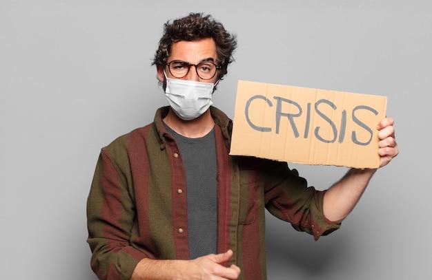 医療マスクと危機ボードを持つ若いひげを生やした男
