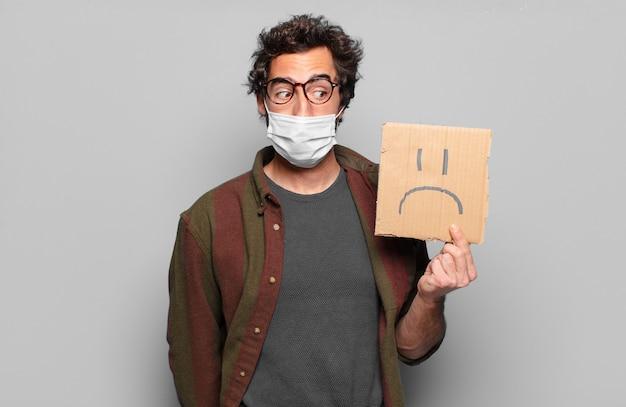 Молодой бородатый мужчина с медицинской маской и грустной концепцией баннера