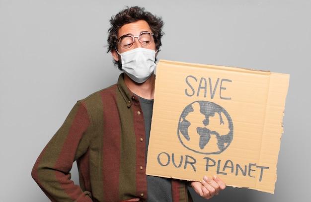 医療マスクを持つ若いひげを生やした男。私たちの惑星の概念を保存します